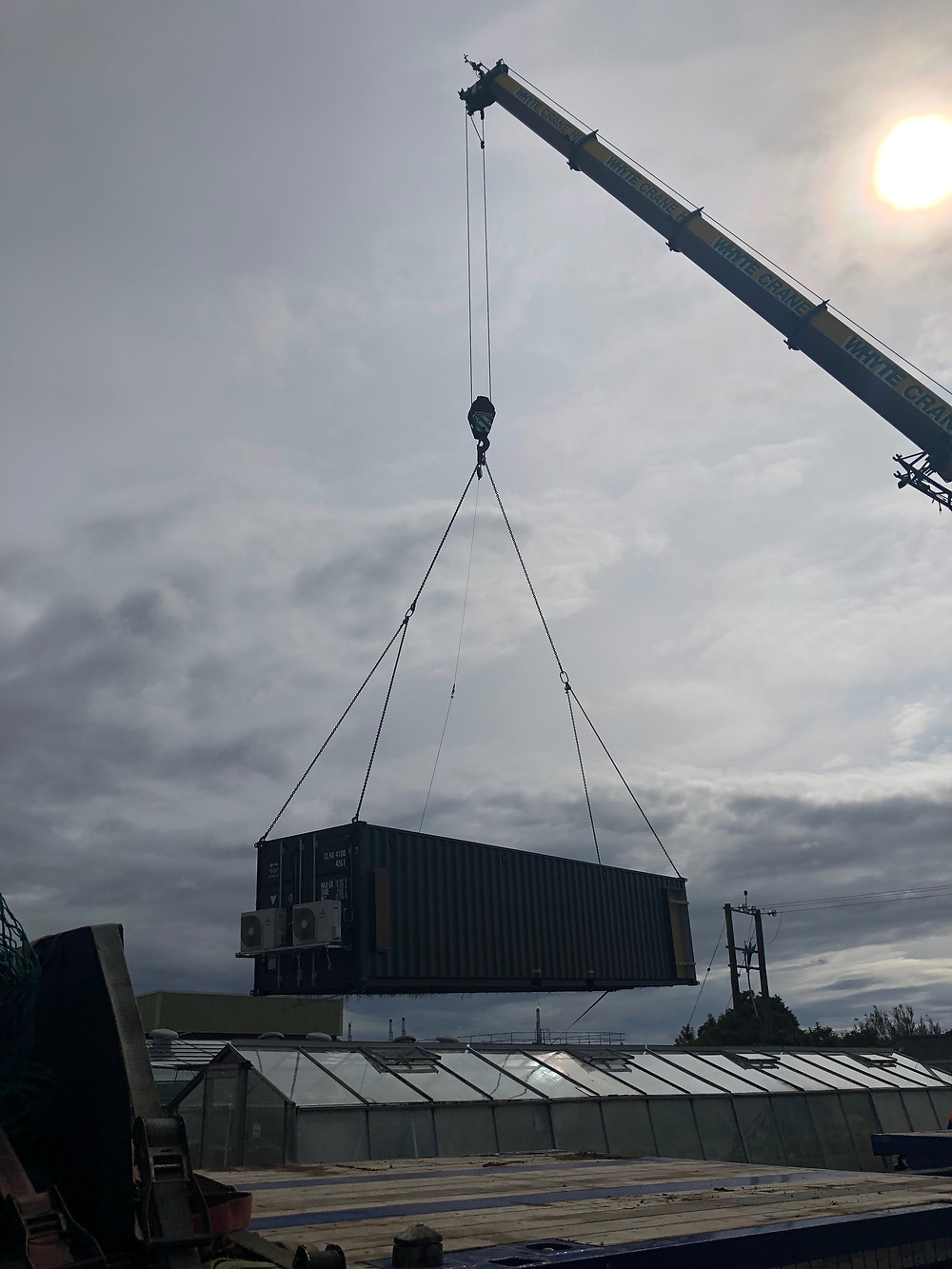 Shipping container vertical farm being lifted into place