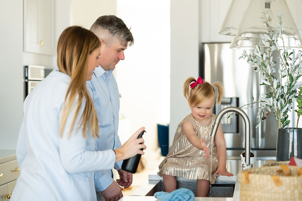 Little girl washing her hands with mom and dad