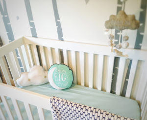 Crib with pillows and mobile at EH Design's Baby K's Modern Nursery