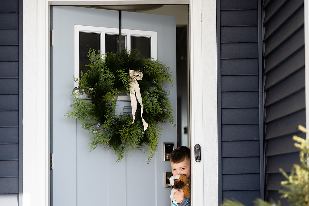 Boy looking out the door with a wreath