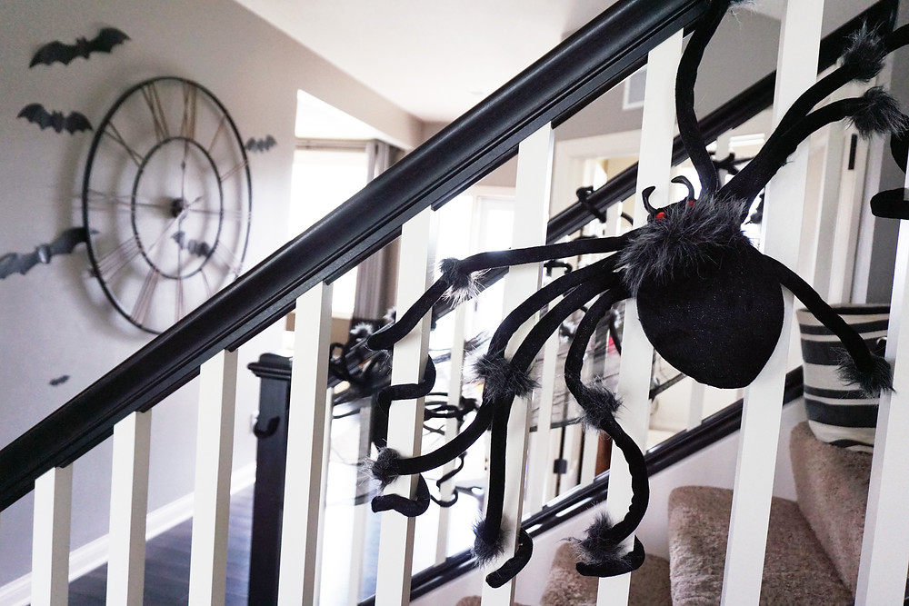 EH Design Blog - Halloween Decorations - Large spiders on banister and view of clock with bats