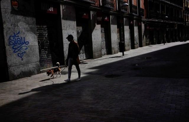 Homem caminha com cachorro em rua de Madrid durante quarentena, neste domingo (5) — Foto: Juan Medina/Reuters