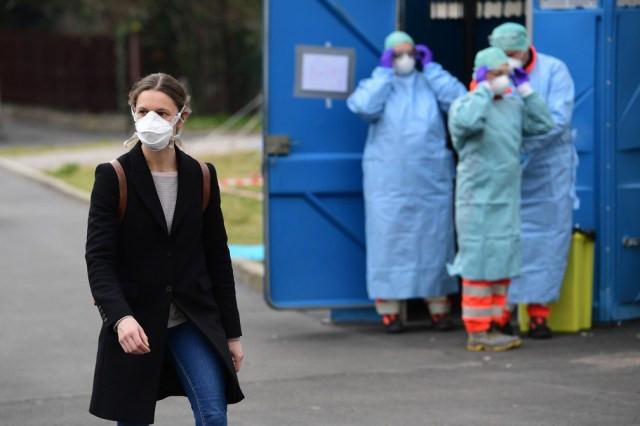 Mulher usando máscara protetora contra a Covid-19 passa em frente a funcionários de hospital de emergência em Brescia, na Lombardia, norte da Itália, nesta sexta (13). — Foto: Miguel Medina/AFP