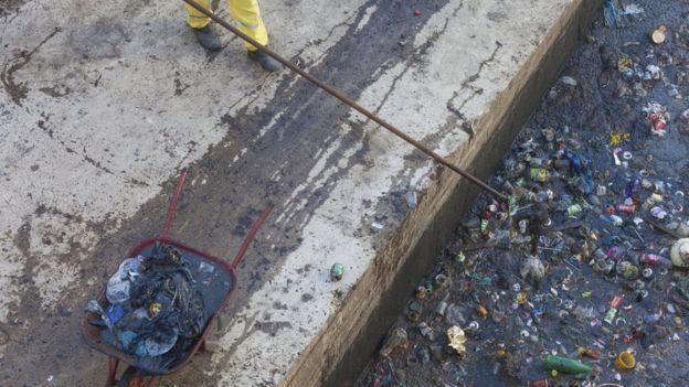 Gari recolhe lixo em um curso d'água