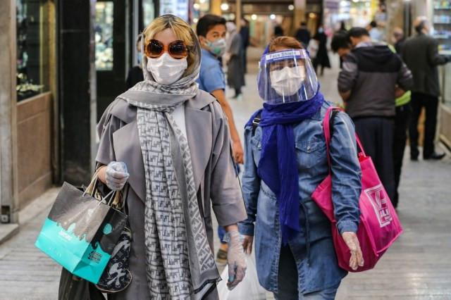 25 de abril: mulheres com máscaras e equipamento de proteção contra a Covid-19 fazem compras em Teerã, no Irã. — Foto: Atta Kenare/AFP