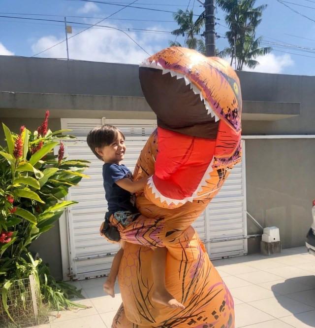 Médico Juan Lambert, fantasiado de dinossauro, abraça o filho Lucca em Caraguatatuba — Foto: Arquivo Pessoal