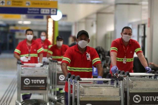 Funcionários do aeroporto usam máscaras para se proteger do novo coronavírus no aeroporto de Guarulhos, em São Paulo, nesta quinta-feira (27). — Foto: Amanda Perobelli/Reuters