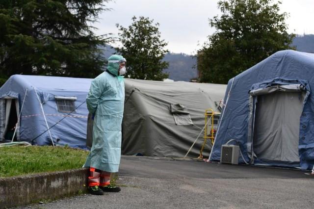 Funcionário de hospital usando equipamento protetor contra a Covid-19 em meio a tendas de emergência montadas em Brescia, na Lombardia, norte da Itália, nesta sexta (13). — Foto: Miguel Medina/AFP