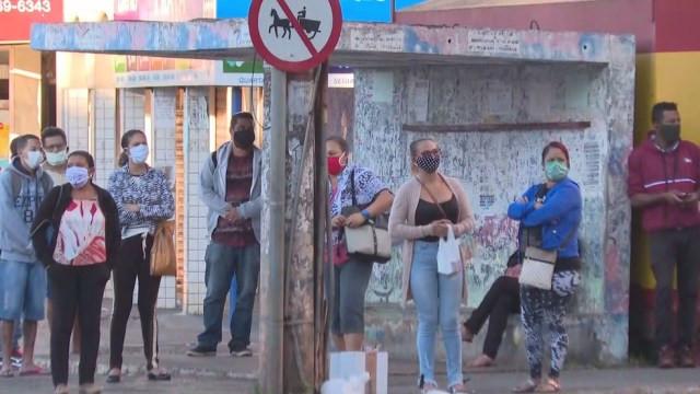 Passageiros à espera de ônibus em parada no DF — Foto: TV Globo/Reprodução