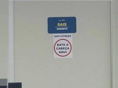"""Cartaz em Secretaria de Saúde do DF sugere que servidores aliviem o estresse: """"Bata a cabeça aqui"""""""
