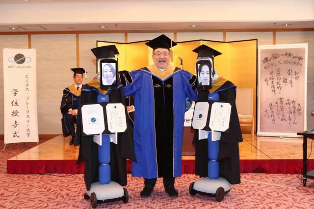 Kenichi Ohmae, presidente da instituição, entrega certificados a alunos representados por robôs