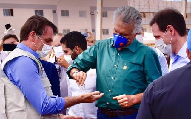 Ronaldo Caiado (DEM) compartilha álcool em gel com presidente Jair Bolsonaro (sem partido) em Águas Lindas de Goiás — Foto: Reprodução/Júnior Guimarães