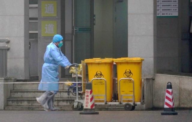 Funcionário remove lixo hospitalar de centro médico de Wuhan, epicentro da epidemia de coronavírus, na China — Foto: AP Photo/Dake Kang