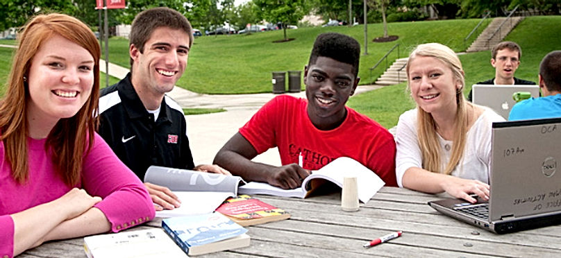 A group of students sit outdoors at a table, smiling, with open books and a laptop at the campus of The Catholic University of America.