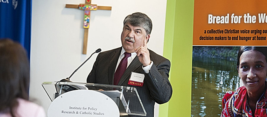 Richard Trumpka, president of the AFL-CIO, speaks at an IPR conference: Erroneous Autonomy, The Dignity of  Work, in 2015.  A crucifix is on the wall behind him and a poster about feeding the poor can be seen.