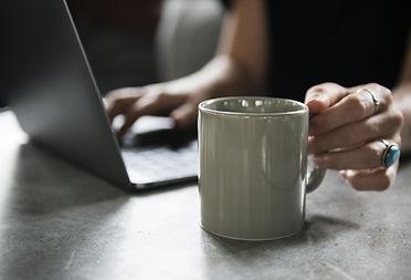 Caneca de bebidas e um laptop