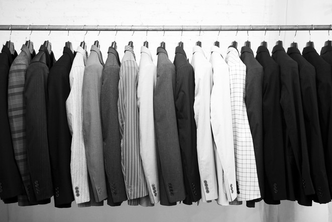 Suits jacket hanging stacked on hanger,b