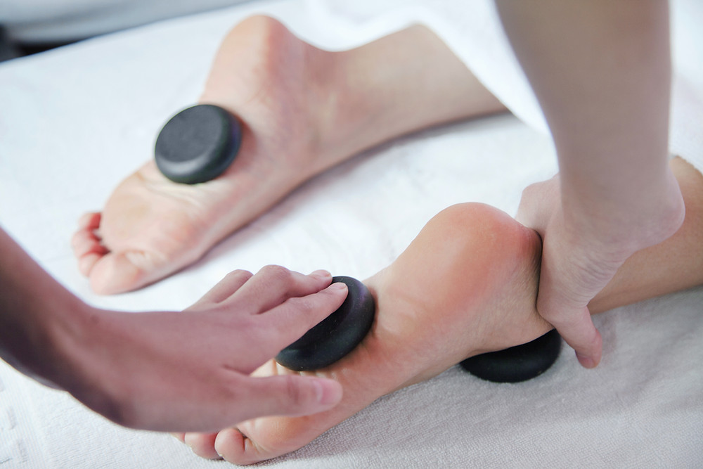 Stones being placed on feet for a spa service.