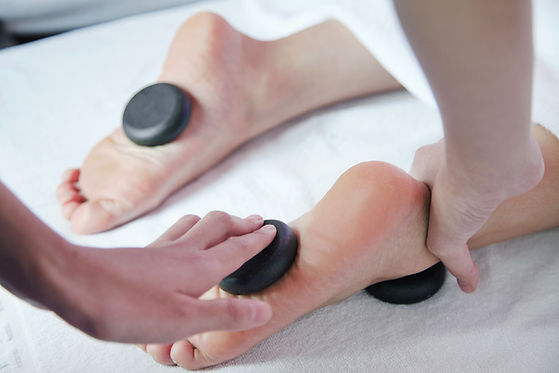 Hot stones being placed on the bottom of a patients foot.