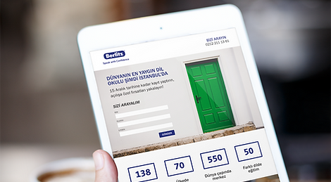 Person holding a tablet dispaying a web page from the web site of Berlitz