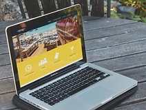 A laptop on a desk showing Fly-inn web site