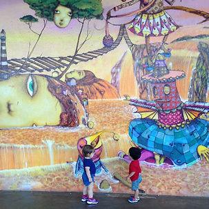 Miguel e outra crianca observam uma parede pintada com uma arte dos artistas Gêmeos.