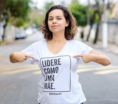 """Foto da Lígia Jalantonio vestindo uma camiseta branca com o seguinte escrito em preto """"lidere como uma mãe"""". A Ligia está num local aberto, a foto tem o fundo desfocado mas percebesse carros e árvores. Lígia aponta com seus dedos indicadores para o escrito da camiseta"""