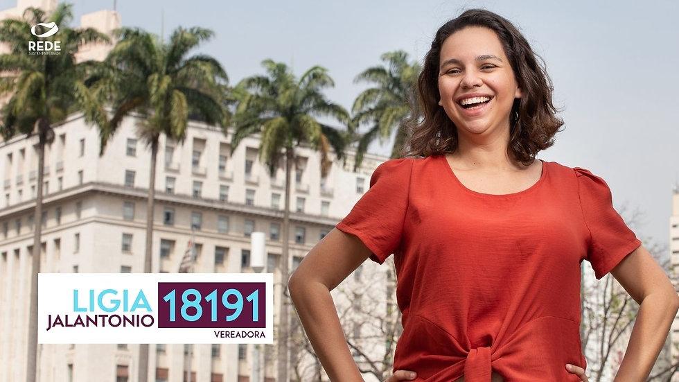 Ligia jalantonio está na frente da sede da prefeitura de São Paulo. Ela está sorrindo, com as mãos na cintura e uma camisa vermelha. Ao lado, um logo com o nome Ligia Jalantonio Vereadora 18191