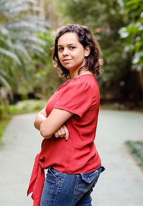 Ligia Jalantonio está de pé e sorrindo levemente. Sua pele é clara e seus cabelos levemente ondulados na altura no ombro e numa cor marro escura. Ligia está com uma blusa vermelha, com os braços cruzados na frente do corpo e de calça jeans. Ela está virada para o lado esquerdo. Atrás há muitas folhas de vários tamanhos e cores de verdes.