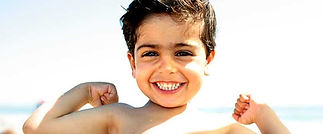 Little-boy-on-beach-showing-his-muscles-