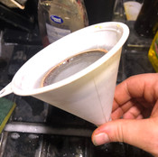A modified funnel with a strainer used to break apart larger clumps