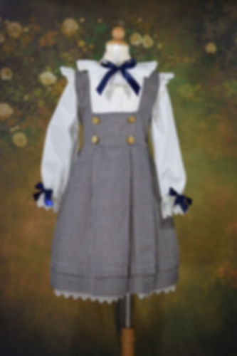 Blue and White Pinafore With Blue Bows and Gold Buttons on Floral Green Backdrop