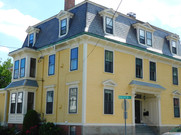 yellow house with concave roofline