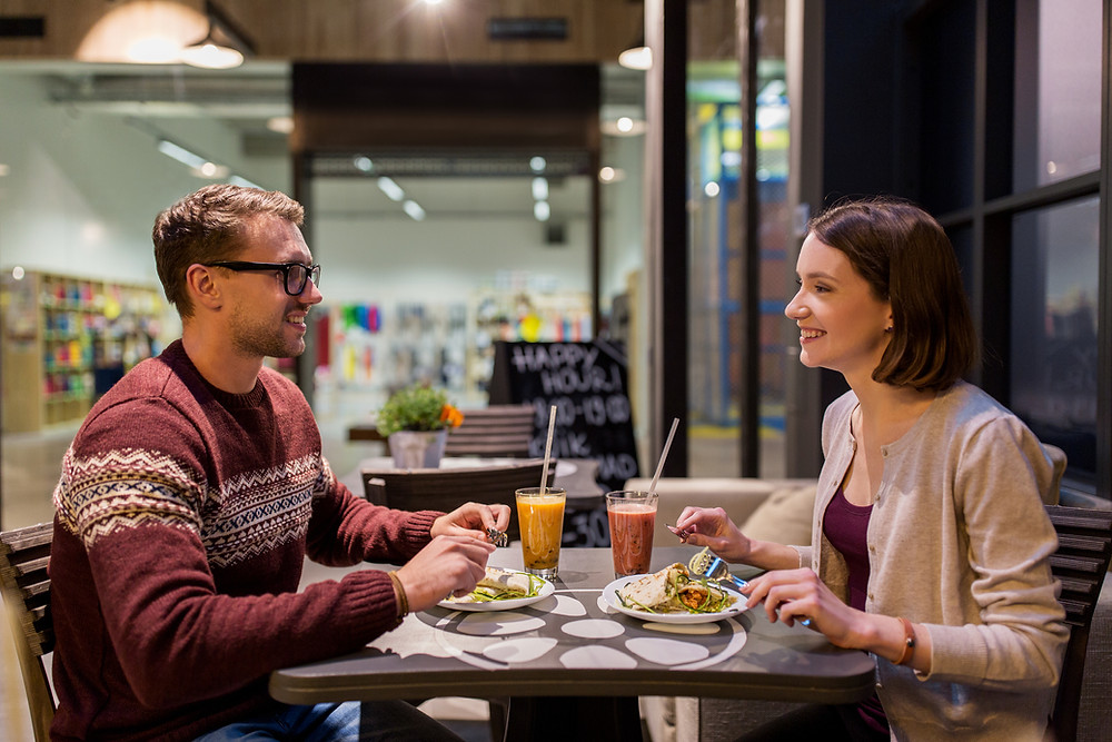 Two people conversing over a meal