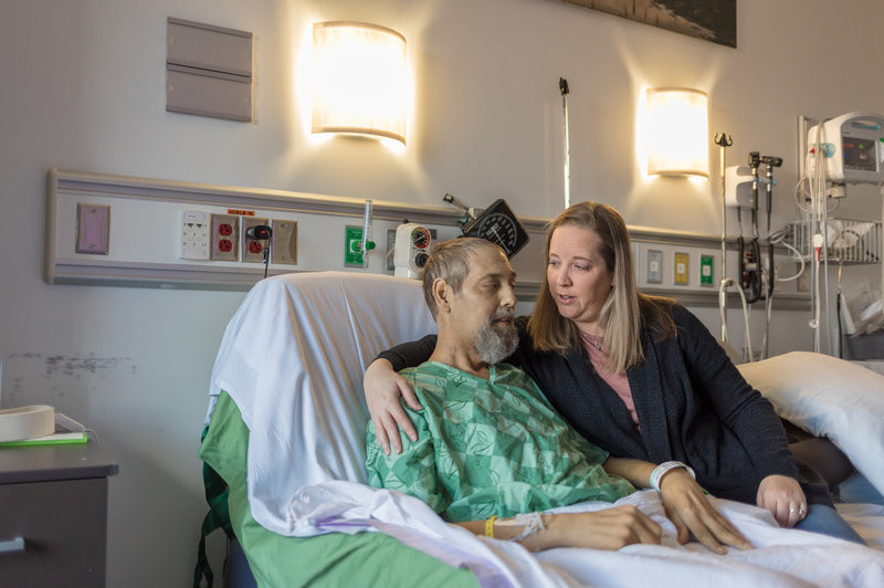 Man in hospital bed with loved one near by