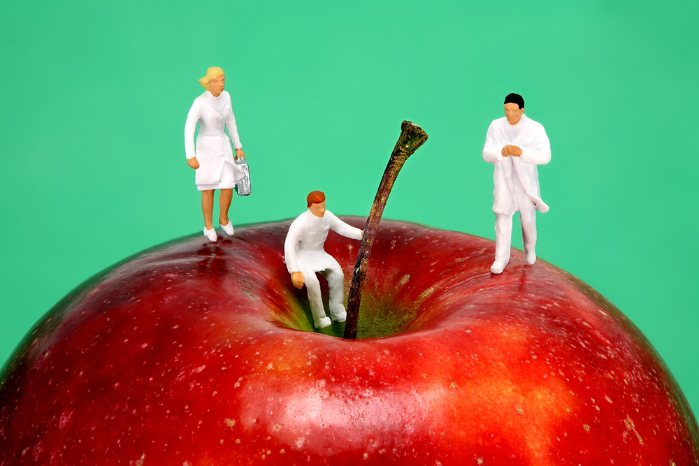 Tiny figurines of medical doctors on a big apple