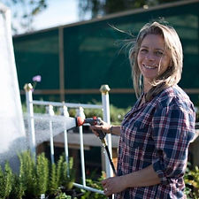 Woman with long blond hair and checked shirt is hosing a vegetable on a sunny day. She is smiling and looking at the camera.