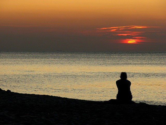 Lonely person on the beach at sunset