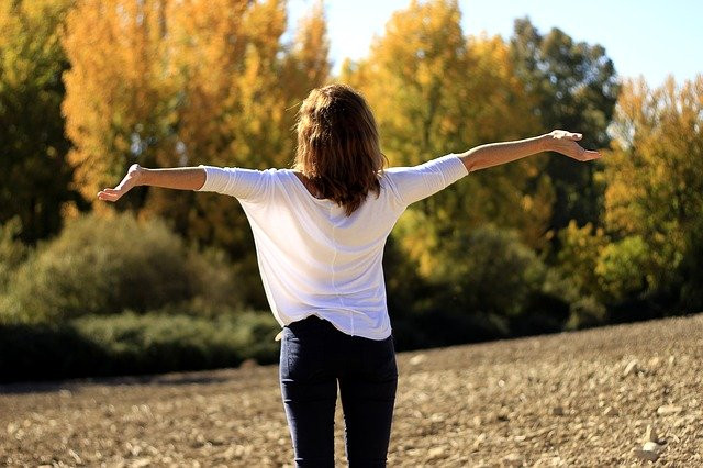 Happy woman with arms wide in the sun