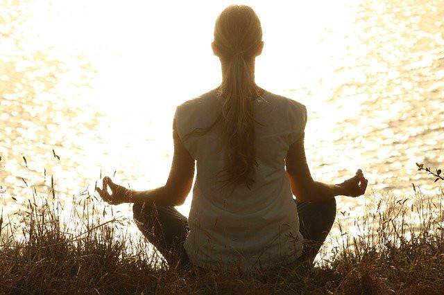 Woman meditating next to water