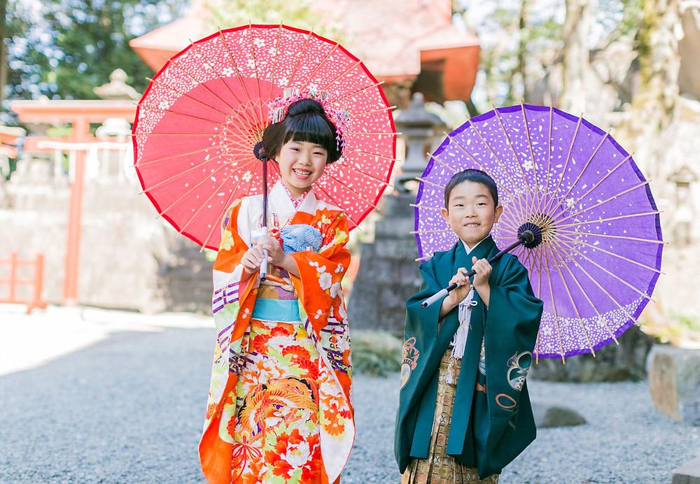 神社で和傘を持つ笑顔の5歳の男の子と7歳の女の子の七五三ロケーション撮影