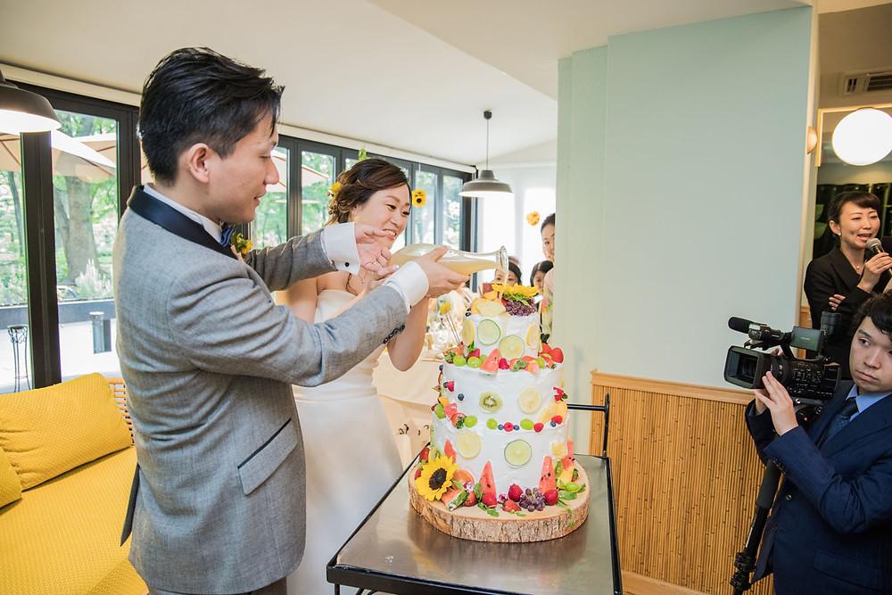 日比谷パレスの結婚式でカラードリップケーキの演出をする新郎新婦の写真