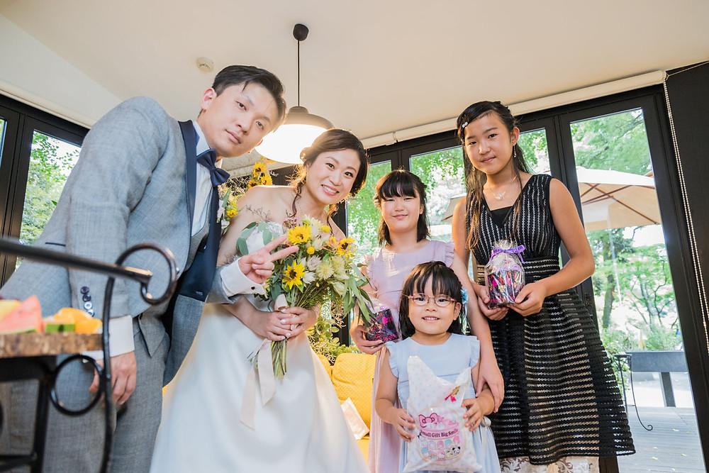 日比谷パレスの結婚式でウエディングケーキの演出のお手伝いをしてくれた子供たちにプレゼントをした新郎新婦と子供たちの写真