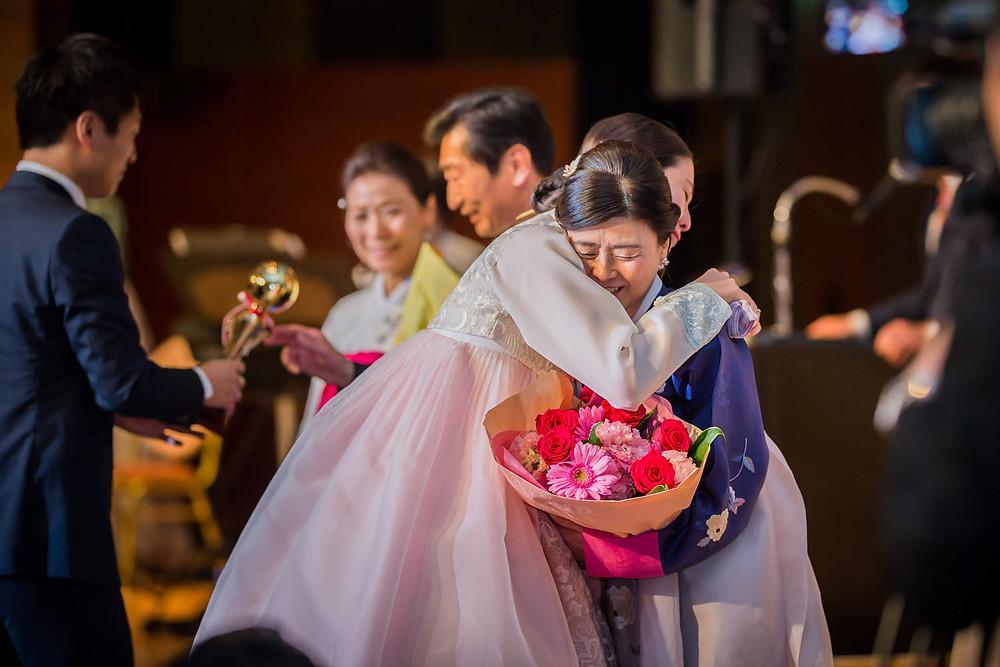 結婚披露宴の新婦手紙の後に両親に花束贈呈をする新郎新婦の写真