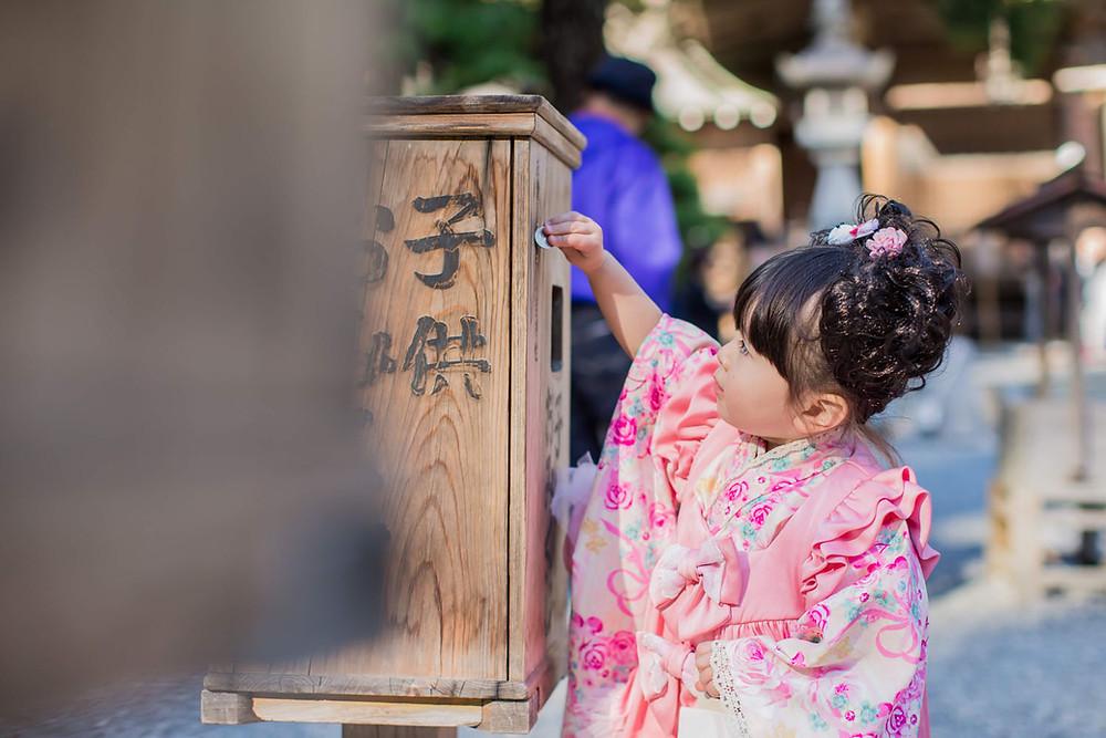 小國神社でおみくじをする3歳女の子の七五三写真