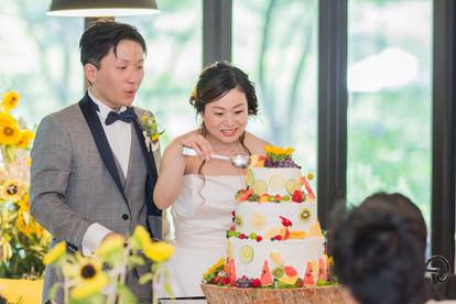日比谷パレスの結婚式でウエディングケーキに盛り付けをする新婦と新郎の写真