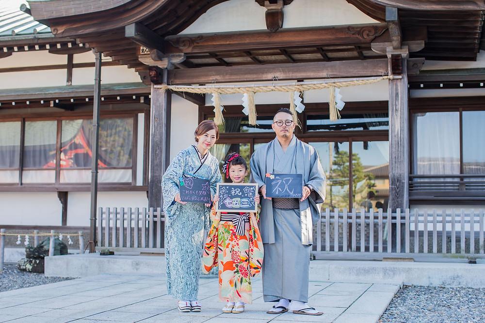 五社神社にて七五三祝いのメッセージを持って撮影した7歳女の子の七五三家族写真