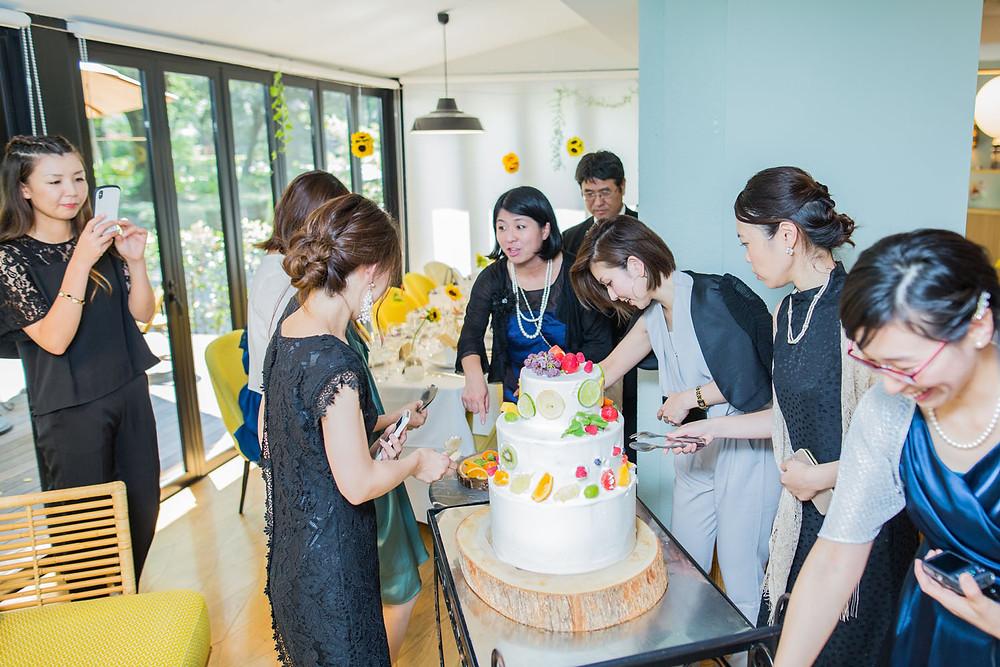 ウエディングケーキをデコレーションするゲストの様子を撮影した写真