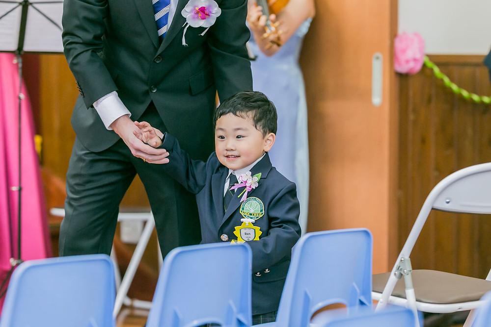 入学式で先生と一緒に入場する男の子の写真