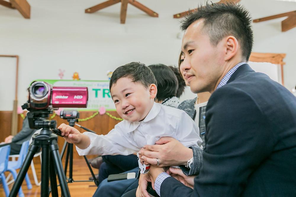 入学式でビデオカメラ撮影をするお父さんと男の子の写真